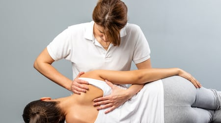 Female therapist manipulating shoulder blade on young female patient.